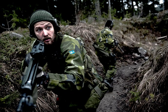 Swedish soldier with rifle in a ditch