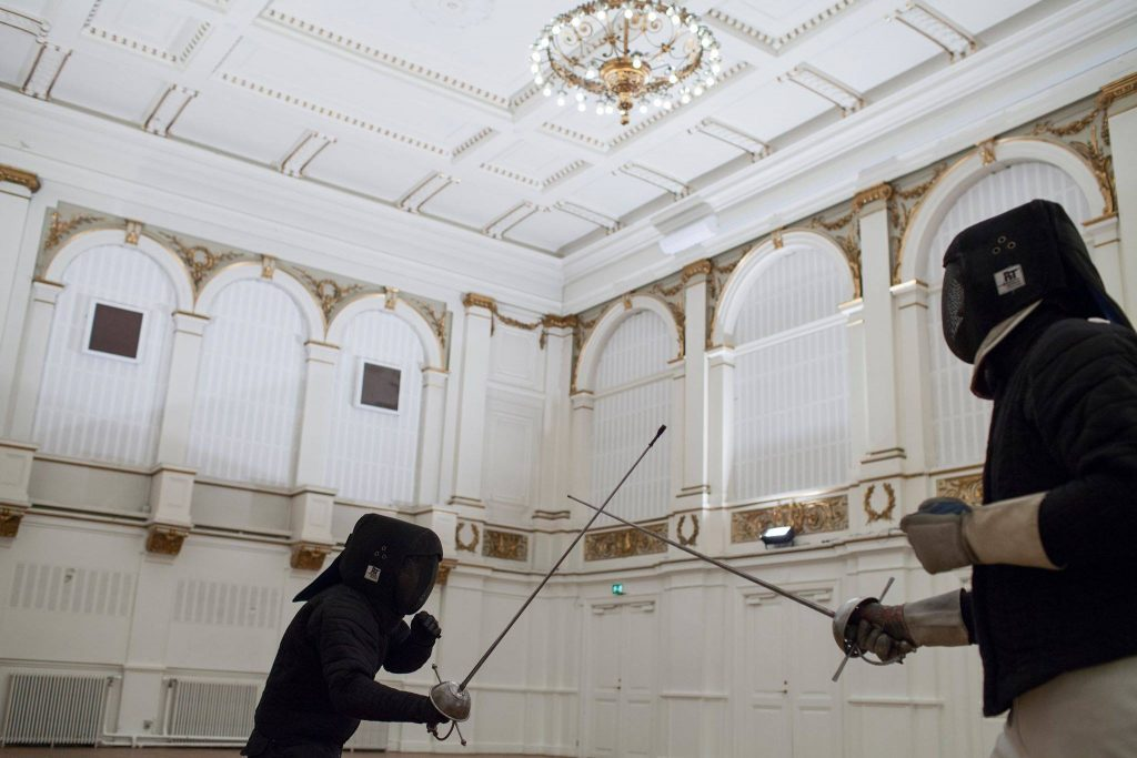 Fencing under chandeliers — Instructor portrait – Historical