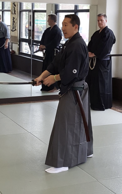 Japanese man in traditional clothing wielding a katana